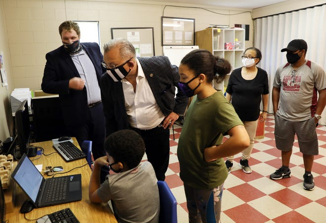 Zanesville Mayor Don Mason looks at a new Chromebook laptop computer with Jayceon Campbell, 7, and his sister Jayda, 9, at the Zanesville Civic League Community Center on Friday. At left is Zanesville Community Development Director Matthew Schley, at right are Lisa Rooks, director of the Zanesville Civic League, and Adonis Brooks, assistant director. The City of Zanesville provided laptops to help students get connected via funding from the CARES act.
