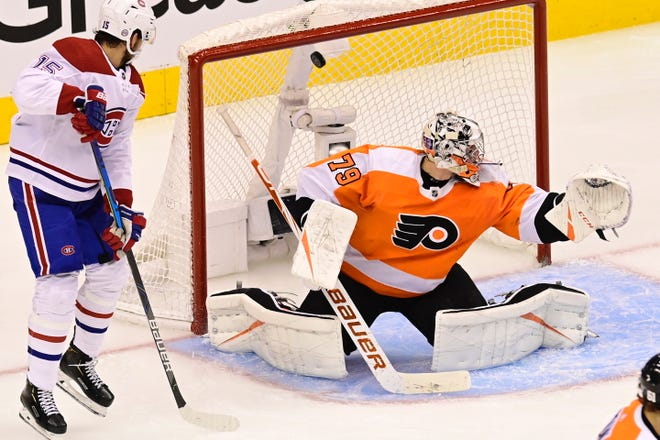 Flyers goalie Carter Hart is unable to stop a shot by the Canadiens' Tomas Tatar, not shown, as Montreal's Jesperi Kotkaniemi looks on during the Flyers' 5-0 Game 3 loss Friday.