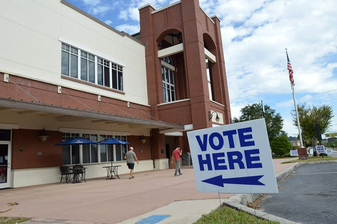 A sign directs people to vote for election day on Tuesday, Nov. 6, 2018, at the Leesburg Public Library.