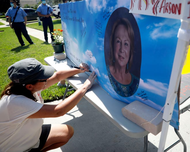 Friends of Betty Adams sign their name at a drive-by memorial service at her Port Orange home on Saturday, Aug. 15. Adams was killed in July.