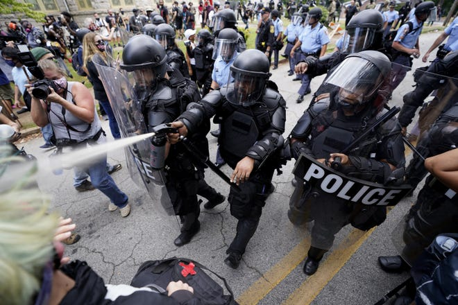 Police clear the streets of some demonstrators with an unknown agent being sprayed during a protest Saturday in Stone Mountain Village, Ga. [John Bazemore/Associated Press]