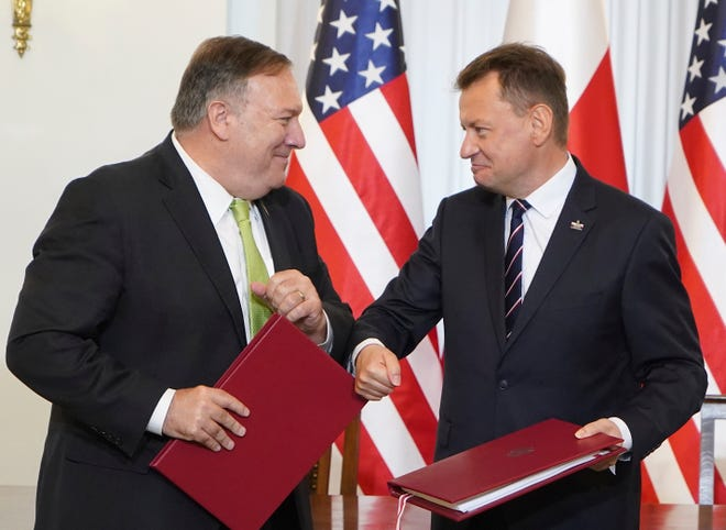 US Secretary of State Mike Pompeo, left, and Poland's Minister of Defence Mariusz Blaszczak greet each other Saturday after signing the US-Poland Enhanced Defence Cooperation Agreement in the Presidential Palace in Warsaw,  Poland. Pompeo is on a five-day visit to central Europe.