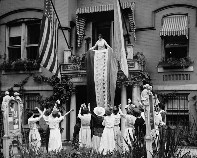 In this Aug. 19, 1920 photo made available by the Library of Congress, Alice Paul, chair of the National Woman's Party, unfurls a banner after the ratification of the 19th Amendment, at the NWP's headquarters in Washington. [LIBRARY OF CONGRESS via AP]