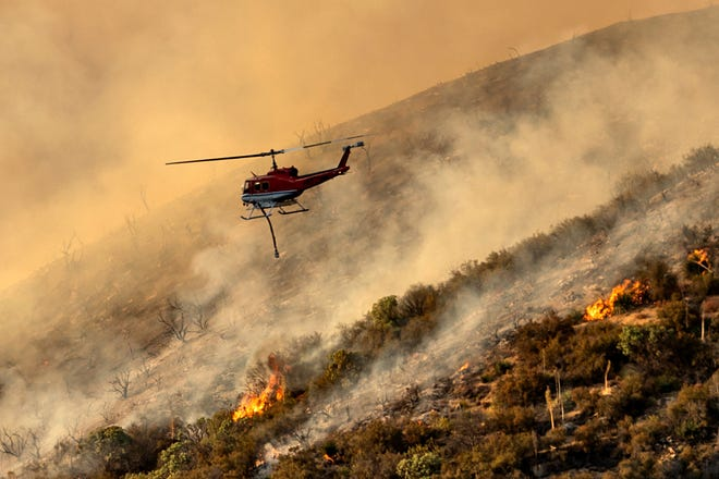 A helicopter prepares to drop water on the Lake Fire burning in the Angeles National Forest north of Santa Clarita, Calif., on Thursday/