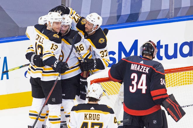 Boston's Charlie Coyle, left, celebrates a goal with Bruins teammates as Carolina Hurricanes goaltender Petr Mrazek, right, looks on during Saturday's third game of the playoff series between the teams.