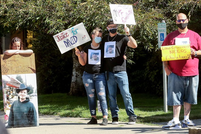 Dezerae Tooley-Aviles and Chaiss Pry, center, wear photos of their friend David Pruitte taped to their shirts as they take part in a peaceful gathering in front of the Kitsap County Courthouse in Port Orchard on Friday. Pruitte, 36, was shot and killed on Aug. 4 by a Kitsap County sheriff's deputy while he was on the Bethel Burley Road overpass above Highway 16.