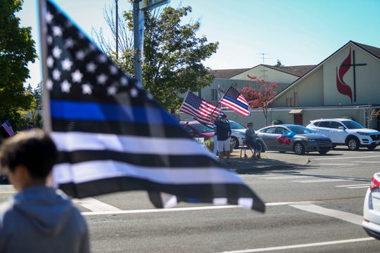 """A crowd gathered on the street and corners near Kitsap Mall in Silverdale on Saturday to show support for law enforcement. They held flags and chanted """"back the blue."""""""