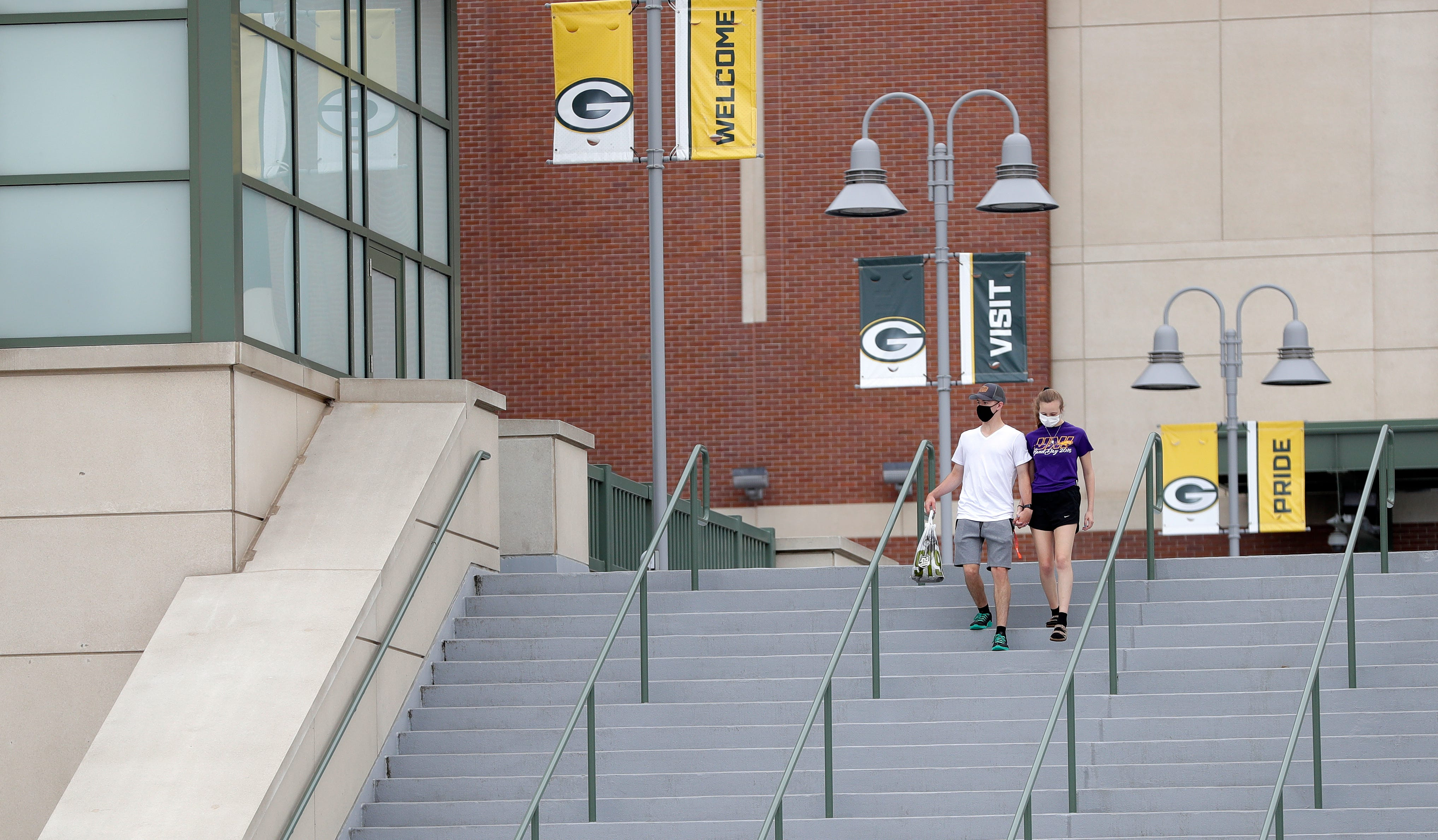 A couple wearing masks walks down the steps at Lambeau Field on Aug. 15, 2020, in Green Bay, Wis. The Green Bay Packers held their first practice of training camp at Ray Nitschke Field, but with no public viewing due to the coronavirus pandemic, only a few fans visited the area.