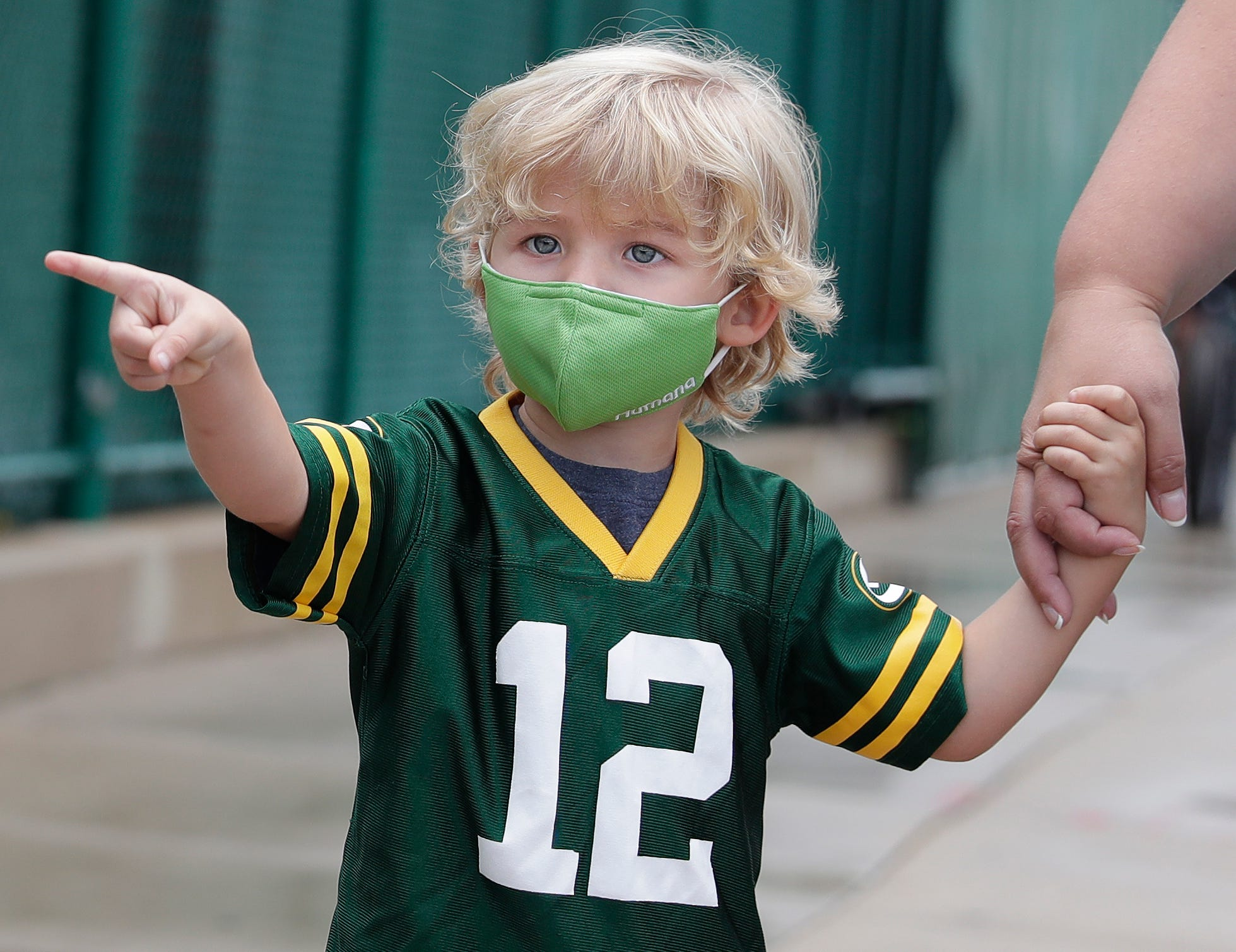 Keegan DeMuth, 3, of Appleton points to Green Bay Packers players at they walk to practice on Aug. 15, 2020, in Ashwaubenon, Wis. The team began its first practice of training camp at Ray Nitschke Field, but with no public viewing due to the coronavirus pandemic, only a few fans visited the area.