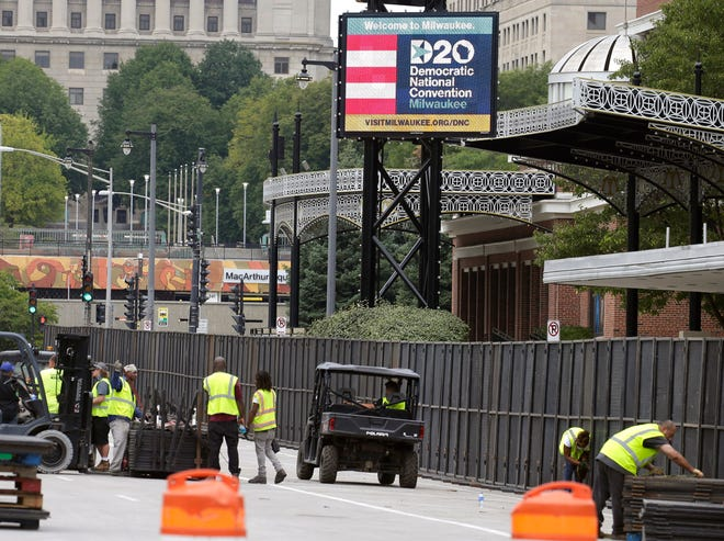 Workers set up additional fencing on West Kilbourn Avenue in downtown Milwaukee Saturday in preparation for the Democratic National Convention Monday through Thursday.