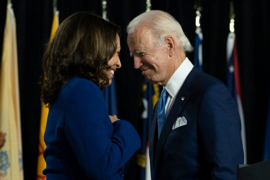 Democratic presidential candidate former Vice President Joe Biden and his running mate Sen. Kamala Harris, D-Calif., pass each other as Harris moves to the podium to speak during a campaign event at Alexis I. duPont High School in Wilmington, Delaware, Wednesday, Aug. 12, 2020.