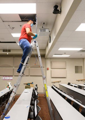 Luis Tovar, of New Mexico State University's Information and Communications Technologies, sets up a hybrid classroom on the Las Cruces campus.