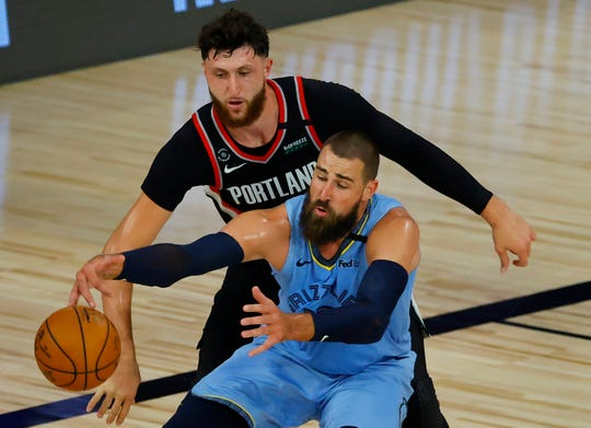 Jonas Valanciunas of the Grizzlies is defended by Jusuf Nurkic of the Trail Blazers during the second quarter.