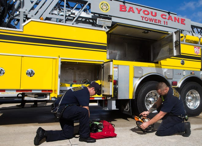 Firefighters Reola Lanegrasse (left) and Chris Adams perform equipment checks at the Bayou Cane Fire Department's main station.