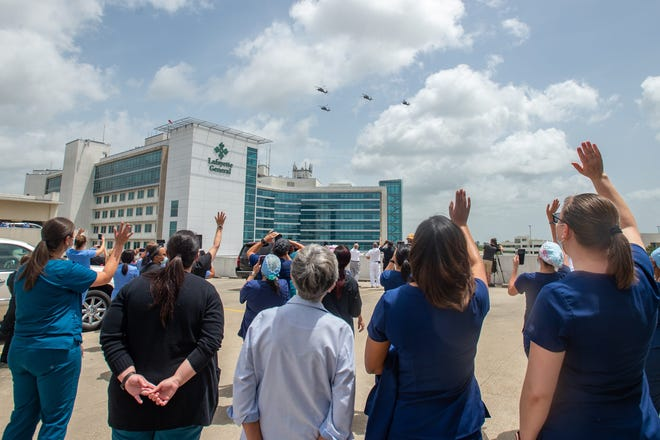 Four Louisiana Army National Guard Black Hawk helicopters fly over Lafayette General Medical Center on July 1 to honor first-responders and health-care professionals who have been working the front lines of the COVID-19 pandemic.