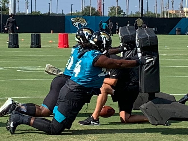 Jaguars defensive linemen Josh Allen (left) and Dawuane Smoot (right) hit a tackling sled during the team's practice on Sunday.