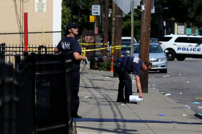 Cincinnati firefighters use bleach to clean and remove pools of blood left at the scene of a mass shooting near Grant Park in the Over-the-Rhine neighborhood of Cincinnati on Sunday. Police confirm that  multiple people are injured and at least three are dead after three separate shootings occurred in the city of Cincinnati within 90 minutes early Sunday morning.