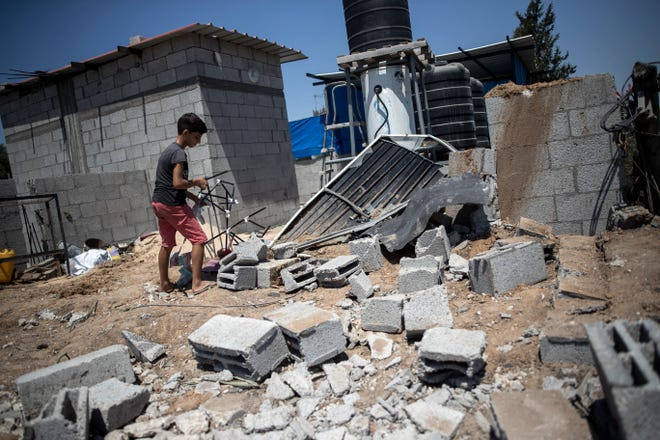 A Palestinian boy inspects the damage in his family home following Israeli airstrikes in Buriej refugee camp, central Gaza Strip, on Saturday.