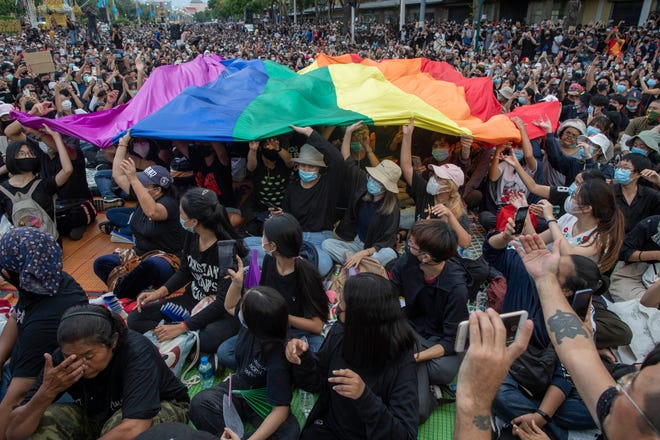 Pro-democracy activists display a LGBT flag during a protest at Democracy Monument in Bangkok, Thailand, on Sunday. Protesters have stepped up pressure on the government  — demanding to dissolve the parliament, hold new elections, amend the constitution and end intimidation of the government's opponents.