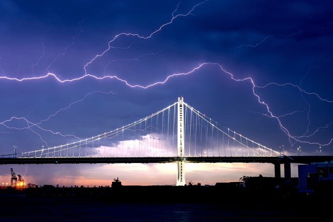 Lightning forks over the San Francisco-Oakland Bay Bridge as a storm passes over Oakland, Calif., on Sunday. Numerous lightning strikes early Sunday sparked brush fires throughout the region.