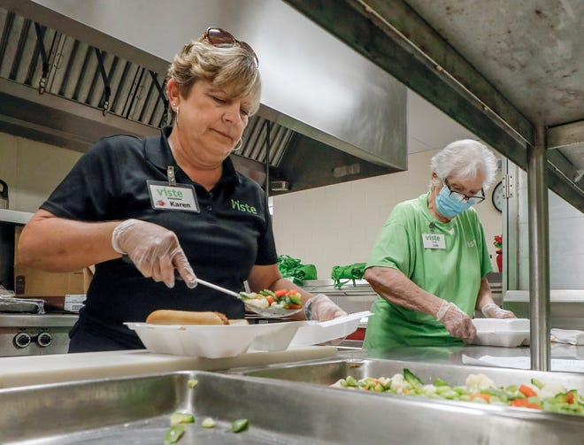 VISTE volunteers, from left, Karen Volkmann and Lois Wathen assemble meals for the elderly at the First Presbyterian Church of Lakeland just as the COVID-19 pandemic was beginning to hit Polk County in late March. VISTE is among the city's nonprofits facing a possible loss in funding due to the pandemic's financial impact. [PIERRE DUCHARME/THE LEDGER]