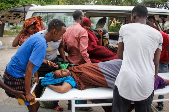 Medical workers and other Somalis help a civilian woman, who was wounded when a powerful car bomb blew off the security gates to the Elite Hotel, as she arrives at a hospital in Mogadishu, Somalia, on Sunday. A Somali police officer says at least 15 people have been killed and more than a dozen others injured in an ongoing siege at the beachside hotel in Somalia's capital where security forces are battling Islamic extremist gunmen who have invaded the building.