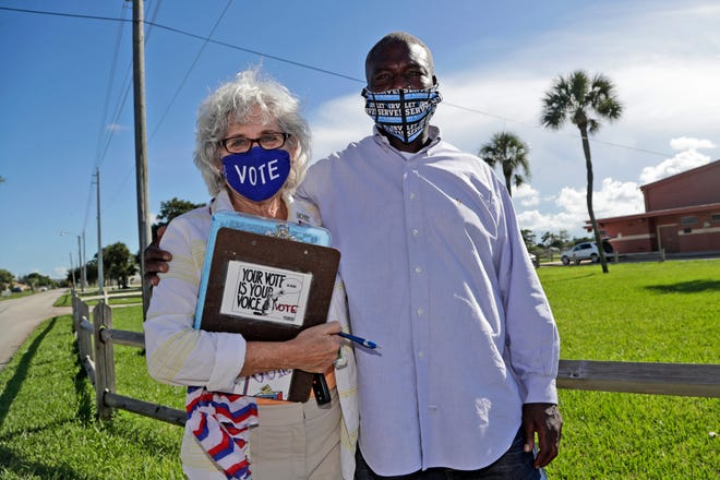 William Freeman, 51, right, poses for a photograph with Arlene Ustin, of the League of Women Voters in Palm Beach County, left, outside of his polling station recently in Riviera Beach.