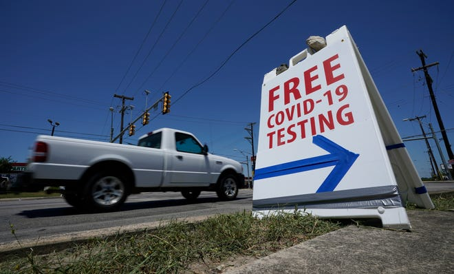 A truck passes a sign for free COVID-19 testing on Friday in San Antonio. Coronavirus testing in Texas has dropped significantly, mirroring nationwide trends, just as schools reopen and football teams charge ahead with plans to play.