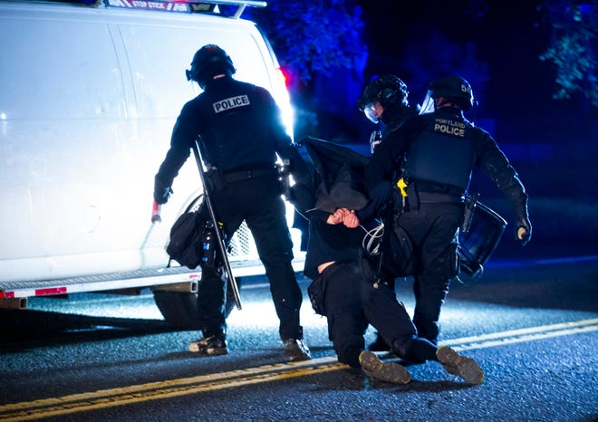 Portland Police detain a protester on Burnside. Police declared a riot near midnight as Portland protests continued for the 80th consecutive night Saturday. Protesters gathered at Laurelhurst Park on Saturday evening before marching to the Penumbra Kelly building.