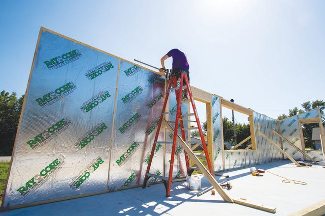 A member of the 2020 Eco Devo/KState build team works on assembling the wall panels for the new eco-friendly affordable home being built in St. John.