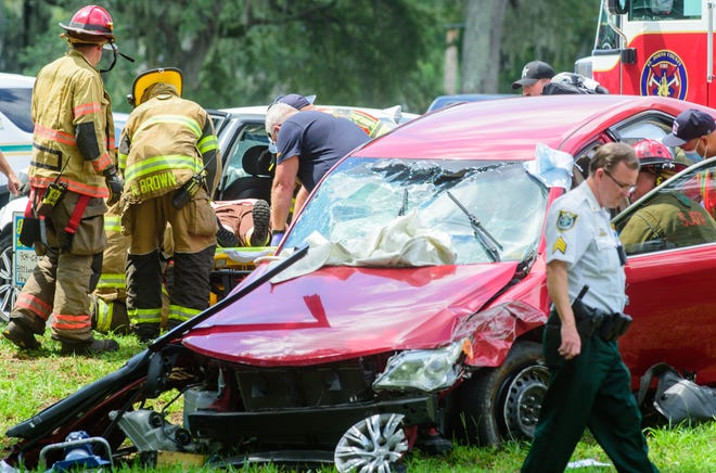 A St. Johns County firefighters treat two woman who were hurt in an accident when the vehicle they were in was in was hit by a car being chased by Flagler and St. Johns County Sheriff deputies at the intersection of Wildwood Drive and U.S. 1 on Sunday, August 16, 2020. [PETER WILLOTT/THE RECORD]