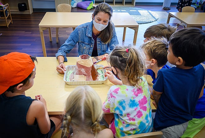 Teacher Emily Mason works with children to paint a model of a volcano during a summer camp held at the Island Prep School in St. Augustine Beach on Friday. [PETER WILLOTT/THE RECORD]