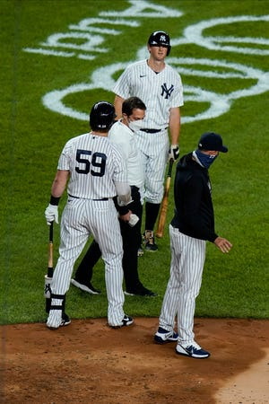 A trainer checks on DJ LeMahieu, above, during his at-bat in the sixth inning Saturday, in New York. LeMahieu later left the game, but the Yankees beat the Red Sox 11-5. (AP Photo/Frank Franklin II)