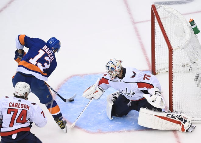 Islanders center Mathew Barzal scores the winning goal past Washington goaltender Braden Holtby during overtime Sunday. (Nathan Denette/The Canadian Press via AP)