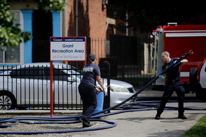 Cincinnati Fire officials clean up the scene of a shooting outside Grant Recreation Area at 40 E. McMicken Avenue on Sunday, August 16, 2020.