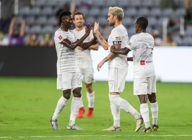 LouCity's Cameron Lancaster gets a high five from teammate Akil Watts, left, after Lancaster scored the game's first goal of the night to put LouCity up 1-0 over visiting Loudoun United in the first half Saturday night. August 15, 2020