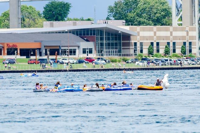 Participants in the 2020 Float Down pass the Blue Water Bridge and the convention center during the unsanctioned event Sunday, Aug. 16, 2020, on the St. Clair River in Port Huron.