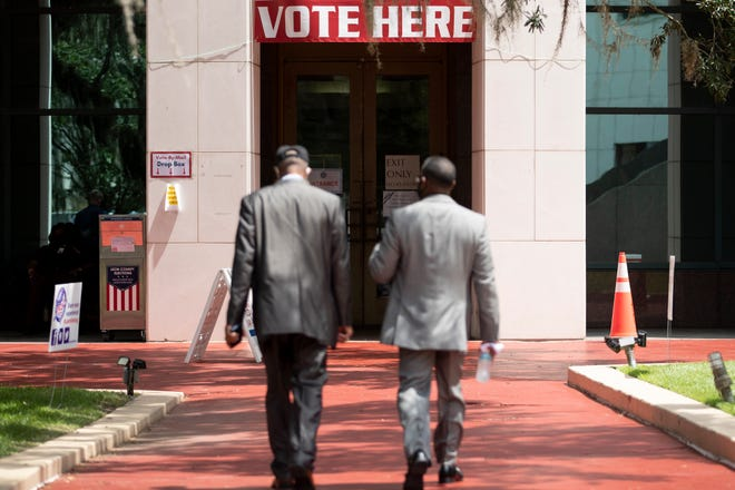 Two men walk towards the entrance to the Leon County Courthouse where early voting went on during the Souls to the Polls event Sunday, August 16, 2020.