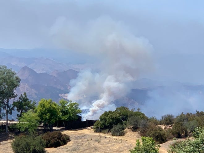 The Rock Fire outside Calabasas as seen from the Saddle Peak neighborhood, southeast of the blaze, shortly before 2 p.m. on Sunday, Aug. 16, 2020.