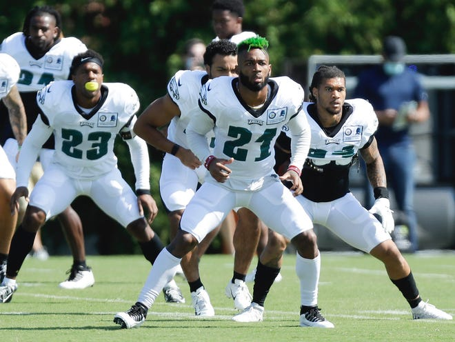Eagles defensive backs Jalen Mills, 21, Rodney McLeod, 23, and their teammates warm up during Monday's first training camp practice. [YONG KIM/POOL PHOTO VIA AP]