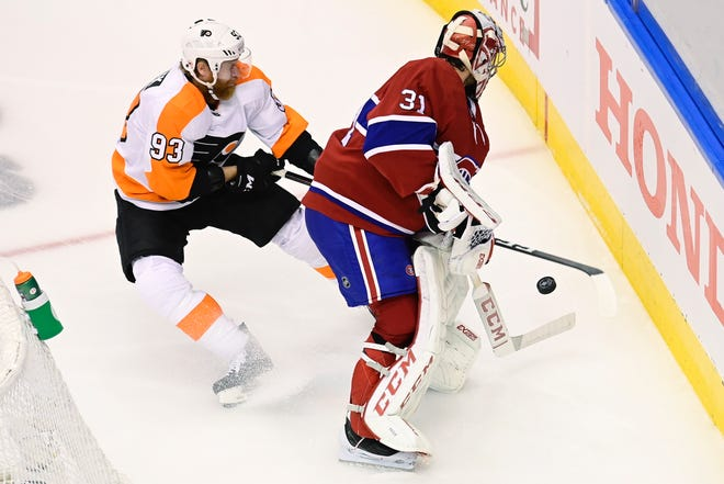 Canadiens goalie Carey Price clears the puck from behind the net as Flyers forward Jakub Voracek contests during Game 2.