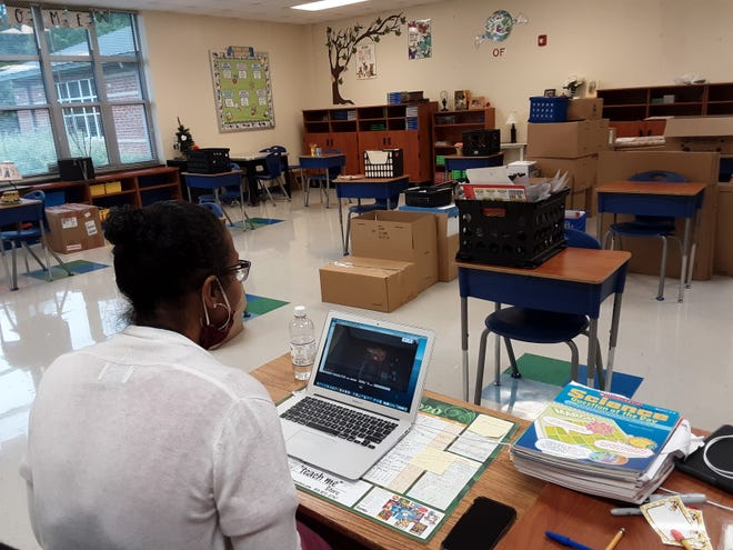 Judy Richards, a teacher at Charles England Elementary School, begins the first day of school in an empty classroom while she connects with her students online.