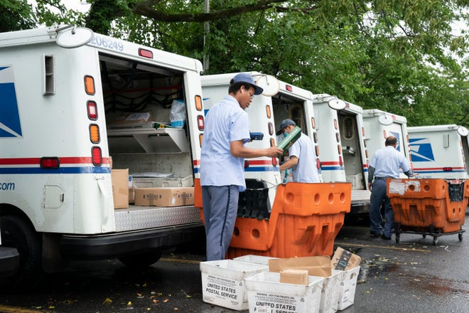Letter carriers load mail trucks for deliveries at a U.S. Postal Service facility in McLean, Virginia, recently. Recent delays in mail processing may make it harder for voters to safely vote from home.