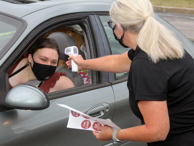 Monmouth College Associate Vice President of Student Life and Co-Dean of Students Michelle Merritt takes the temperature of a driver arriving on campus on Saturday morning. The liberal arts college's fall semester begins Tuesday.