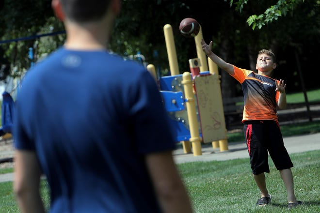 Kaiden Shull, 10, Mount Pleasant, tosses a football around with his cousin Christian Herod, 18, Danville, Aug. 7, 2020 at the Pat Klein Park in West Burlington. The two, who were in town to get haircuts were having lunch in the park with other family members following their game of catch.