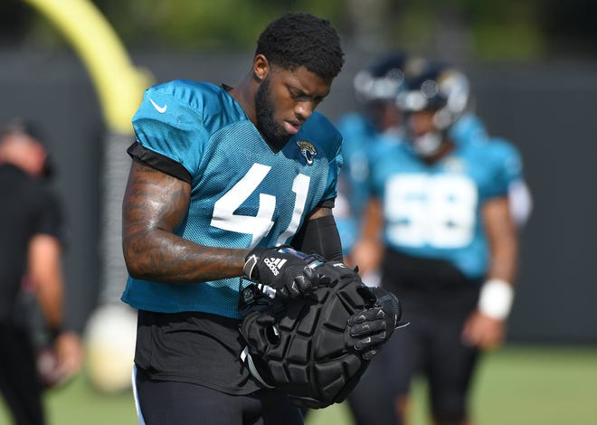 Jaguars defensive end Josh Allen adjusts the extra padding for his helmet during Monday's practice. It was the first padded practice of training camp. Bob Self/Florida Times-Union