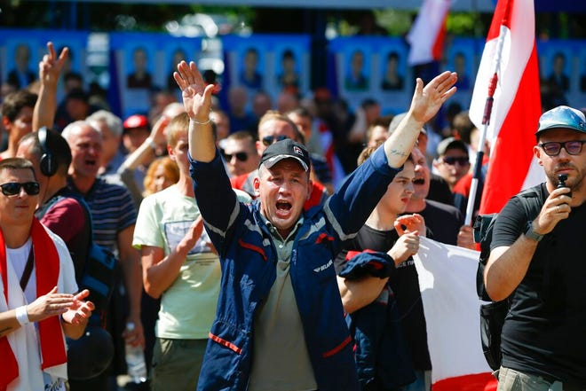 Workers with old Belarus national flags shout anti-Lukashenko slogans during a rally at the Minsk Motor Plant in Minsk, Belarus, Monday, Aug. 17, 2020.  Some thousands of factory workers have taken to the streets of Minsk demanding the resignation of Belarus' authoritarian President Alexander Lukashenko. (AP Photo/Sergei Grits)