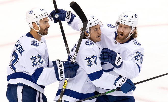 Tampa Bay Lightning center Yanni Gourde (37) is congratulated on his goal by defenseman Kevin Shattenkirk (22) and center Blake Coleman (20) after scoring against the Columbus Blue Jackets during the second period of NHL Eastern Conference Stanley Cup first round playoff action in Toronto on Monday.