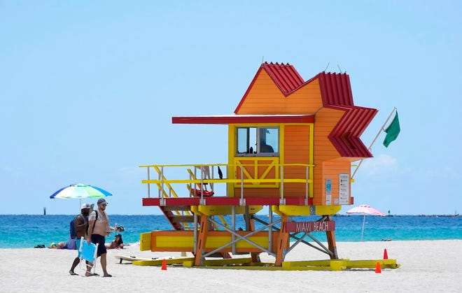 FILE - In this Aug. 11, 2020, file photo, beachgoers walk past one of the lifeguard towers designed by architect William Lane during the coronavirus pandemic, on Miami Beach, Florida's famed South Beach. As states around the country require visitors from areas with high rates of coronavirus infections to quarantine upon arrival, children taking end-of-summer vacations to hot spots are facing the possibility of being forced to skip the start of in-person learning at their schools. (AP Photo/Wilfredo Lee)