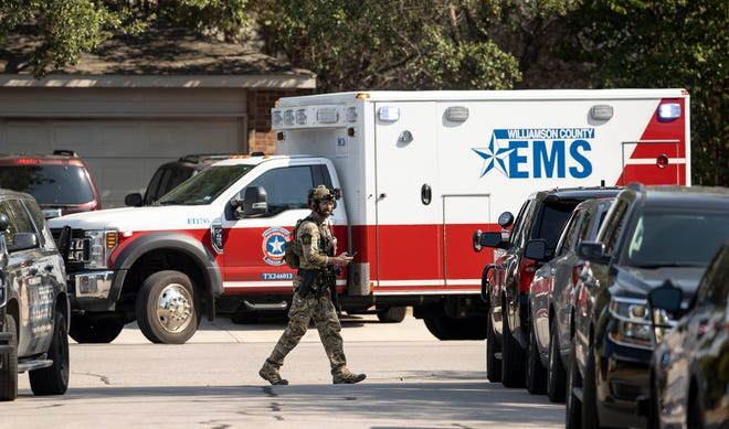 A police officer works at the scene of a standoff in Cedar Park, Texas, on Sunday.